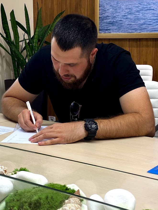 Yevgeniy Nikolov signs the final compensation agreement in the MTWTU office